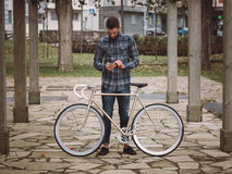 Hipster man with a fixie bike and smartphone Stock Photos