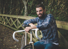 Hipster man with a fixie bike and smiling Royalty Free Stock Images