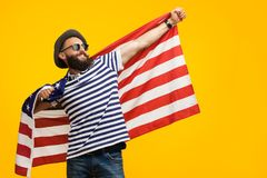 Hipster man with flag on orange. Young hipster in hat and sunglasses posing cheerfully with American flag looking away on orange background Stock Photos