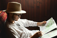 Hipster man in glasses  looking at map and exploring, sitting on Royalty Free Stock Images