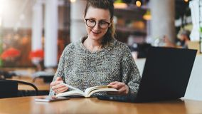 Hipster man in glasses is sitting in cafe, reading notes in notebook. On table is laptop.Freelancer works remotely. Young hipster girl in glasses is sitting in royalty free stock photography