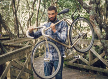 Hipster man holding his bicycle stock image