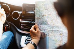 Hipster man holding in male hands and looking on navigation map in auto, tourist traveler hiker driving on background panoramic vi. Ew way road, trip in stock images