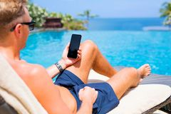 Man holding mobile phone while relaxing by the pool. Hipster man holding mobile phone while relaxing by the pool royalty free stock image