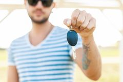 Hipster man holds the key. A man in a striped T-shirt holds a car key in his hand stock photos