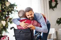 A hipster man hugging his senior father in wheelchair at Christmas time. A hipster men hugging his disabled senior father in wheelchair at Christmas time stock image