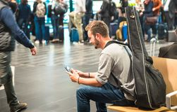 Hipster man at international airport using mobile smart phone. Wanderer person at terminal gate waiting for airplane - Wanderlust travel trip concept with guy Stock Photos