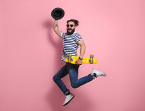 Hipster man jumping with longboard. Young hipster stylish man in sunglasses and hat holding yellow longboard and jumping on pink background Stock Photo