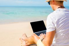 Man with laptop on the beach. Hipster man with laptop on the beach stock photography