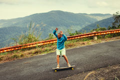 Hipster man longboarding extremely action in highway tropics Stock Photos