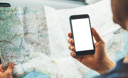Hipster man looking on navigation map in car, tourist traveler driving and holding in male hands smartphone gps with clean screen. Display, panoramic view way Royalty Free Stock Images