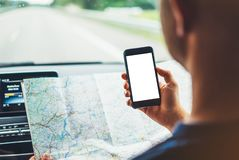 Hipster man looking on navigation map in car, tourist traveler driving and holding in male hands smartphone gps with clean screen. Display, panoramic view way royalty free stock photo