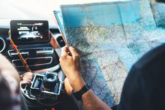 Hipster man looking and point finger on location navigation map in car, tourist traveler driving and hold in male hands europe car. Tography, view and plan royalty free stock images