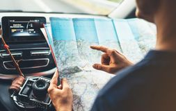 Hipster man looking and point finger on location navigation map in car, tourist traveler driving and hold in male hands europe car. Tography, view and plan Stock Image