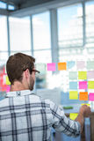 Hipster man looking at post-it Royalty Free Stock Photos