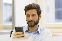 Hipster man in office. Typing text message  on mobile phone. Handsome man looking at his smartphone at work Royalty Free Stock Image