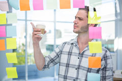 Hipster man pointing at post-it Royalty Free Stock Images