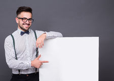 Hipster man posing with blank poster. Hipster man posing with poster isolated on grey background. Short-haired man in white shirt pointing to something on the royalty free stock photos