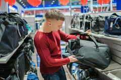 Hipster man purchasing stylish backpack in supermarket store. Young hipster man purchasing stylish backpack in supermarket store Royalty Free Stock Photo
