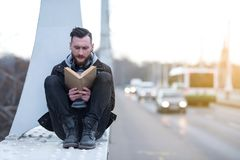 Hipster man reading on a bridge Royalty Free Stock Image