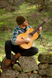 Hipster man with red beard with a guitar in the field Stock Photo