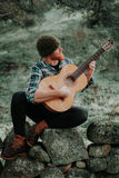 Hipster man with red beard with a guitar in the field Royalty Free Stock Images
