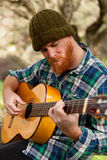 Hipster man with red beard playing a guitar Royalty Free Stock Photo