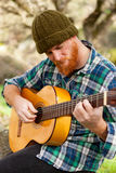 Hipster man with red beard playing a guitar Royalty Free Stock Image