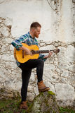 Hipster man with red beard playing a guitar Stock Image