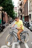 Hipster Man on retro bicycle have a stop to see a map in european city. Tourism concept. Vacation. royalty free stock images