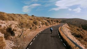 Hipster man rides on skateboard on mountain road. Beautiful and epic shot from drone of lonely figure of teenager or man skateboard down mountain road on amazing stock video