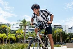 Hipster man riding bike in the city. Hipster man riding bike outdoor in the city in the summer royalty free stock photography