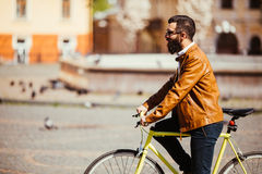 Hipster man riding in a fixie bike in the sunny city streets. Stock Images