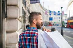 Hipster man shopping , streets of London, back view Stock Photo