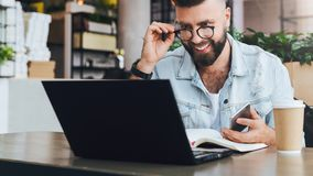 Hipster man sits in cafe, uses smartphone, works on laptop. Businessman reads information message on computer screen. stock photo