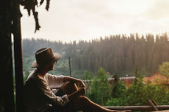 Hipster man sitting on porch of wooden house  looking at woods i Stock Photography