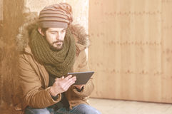 Hipster man sitting using tablet with a warm tone filter applied Royalty Free Stock Photography