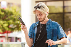 Hipster man standing on city street listening music. Men fashion, technology, urban style clothing concept. Hipster guy standing on city street wearing jeans Royalty Free Stock Photos