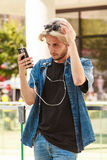 Hipster man standing on city street listening music. Men fashion, technology, urban style clothing concept. Hipster guy standing on city street wearing jeans Stock Images