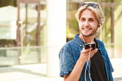 Hipster man standing on city street listening music. Men fashion, technology, urban style clothing concept. Hipster smiling guy standing on city street wearing Royalty Free Stock Photography