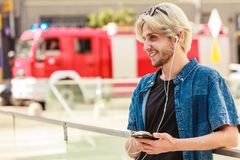 Hipster man standing on city street listening music. Men fashion, technology, urban style clothing concept. Hipster smiling guy standing on city street wearing Royalty Free Stock Image