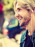 Hipster man standing on city street listening music Stock Image