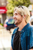 Hipster man standing on city street listening music. Men fashion, technology, urban style clothing concept. Hipster smiling guy standing on city street wearing Stock Images