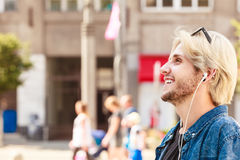 Hipster man standing on city street listening music Royalty Free Stock Photography