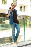 Hipster man standing with earphones talking on phone Stock Photography