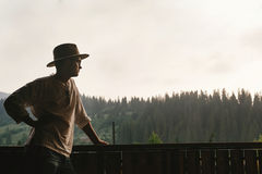 Hipster man standing on porch of wooden house and relaxing looki. Ng at mountains in evening, calm moment, summer vacation concept, space for text Royalty Free Stock Photography