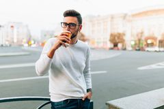 Hipster man standing with takeaway coffee, smiling plesantly, walking on th city street. Happy carefree handsome guy in eyewear royalty free stock photography