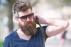 Hipster man with stylish beard and mustache walking in city. Closeup portrait of handsome young man in trendy eyewear stock photos