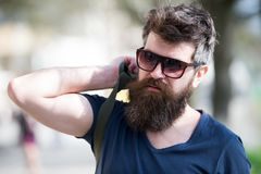 Hipster man with stylish beard and mustache walking in city. Closeup portrait of handsome young man in trendy eyewear. Outdoors stock photography