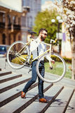 Hipster man in sunglasses carrying on his shoulder bike on street stairs. A young handsome man with beard holding bike on his righ Stock Photos